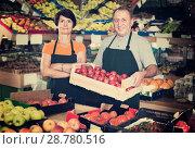 Купить «Sellers demonstraiting tomatos in store», фото № 28780516, снято 22 октября 2017 г. (c) Яков Филимонов / Фотобанк Лори