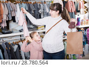 Купить «Mom considering options for dresses for newborn», фото № 28780564, снято 10 января 2017 г. (c) Яков Филимонов / Фотобанк Лори