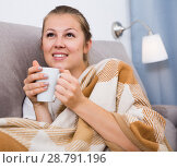 Купить «Young woman is sitting in plaide and drinking tea», фото № 28791196, снято 22 октября 2018 г. (c) Яков Филимонов / Фотобанк Лори