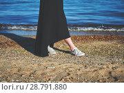 Купить «Female feet in white sneakers on sand. Walk along the beach. Woman wearing black dress. Retro toned image», фото № 28791880, снято 28 апреля 2018 г. (c) Вдовиченко Денис / Фотобанк Лори