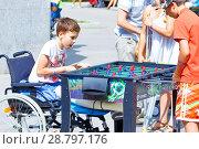 Купить «Russia, Samara, July 2017: a boy in a wheelchair playing table tennis on the Volga River Embankment on a summer sunny day», фото № 28797176, снято 12 августа 2017 г. (c) Акиньшин Владимир / Фотобанк Лори
