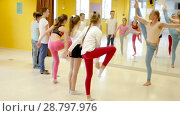 Купить «Teenage boys and girls practicing dance, stretching with female trainer in dance hall», видеоролик № 28797976, снято 26 марта 2018 г. (c) Яков Филимонов / Фотобанк Лори