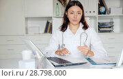 Купить «Portrait of young woman doctor in white uniform standing in clinic's office», видеоролик № 28798000, снято 21 мая 2018 г. (c) Яков Филимонов / Фотобанк Лори