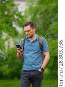 Купить «young man using mobile phone in the forest while hiking», фото № 28803736, снято 28 июня 2018 г. (c) Иван Карпов / Фотобанк Лори