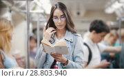 Купить «Girl holding on to the handrail and reading a book on the subway train, slow motion», видеоролик № 28803940, снято 22 июля 2018 г. (c) Константин Шишкин / Фотобанк Лори