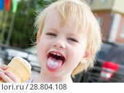 Купить «Маленькая девочка ест мороженое на улице города», фото № 28804108, снято 6 июня 2018 г. (c) Момотюк Сергей / Фотобанк Лори