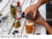 Купить «Мужчина наливает свежее пиво в кружку во время игры в домино во дворе дома», фото № 28804796, снято 21 июля 2018 г. (c) Николай Винокуров / Фотобанк Лори