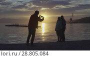 Купить «Друзья фотографируются на фоне красочного заката над Тихим океаном», видеоролик № 28805084, снято 10 июля 2018 г. (c) А. А. Пирагис / Фотобанк Лори