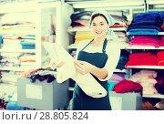 Купить «Seller showing white fabric», фото № 28805824, снято 4 января 2017 г. (c) Яков Филимонов / Фотобанк Лори