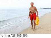 Купить «Cheery man in beachwear resting near ocean», фото № 28805896, снято 16 июня 2018 г. (c) Яков Филимонов / Фотобанк Лори