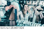 Купить «Smiling girl is enjoying her purchases», фото № 28807924, снято 20 марта 2017 г. (c) Яков Филимонов / Фотобанк Лори