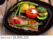 Купить «Grilled veal loin with vegetables and redcurrant on wooden background», фото № 28808220, снято 27 июня 2018 г. (c) Яков Филимонов / Фотобанк Лори