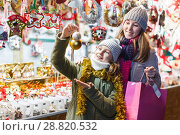 Купить «Smiling girl with woman are buying toys for X-mas tree», фото № 28820532, снято 19 декабря 2017 г. (c) Яков Филимонов / Фотобанк Лори