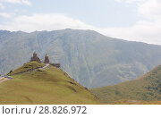 Купить «Tsminda Sameba- Holy Trinity Church near the Kazbegi-Gergeti village.The Church is situated at an altitude of 2300 meters at the foot of mount Kazbek», фото № 28826972, снято 18 августа 2013 г. (c) Олег Хархан / Фотобанк Лори
