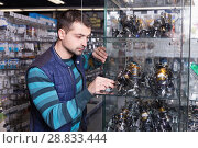 Купить «Young man looking new baitcasting reel for rod in shop», фото № 28833444, снято 16 января 2018 г. (c) Яков Филимонов / Фотобанк Лори