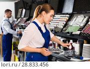 Купить «Smiling female car painter preparing paints for paintwork in modern auto repair shop», фото № 28833456, снято 4 апреля 2018 г. (c) Яков Филимонов / Фотобанк Лори