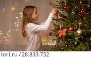 Купить «happy girl decorating christmas tree at home», видеоролик № 28833732, снято 26 июля 2018 г. (c) Syda Productions / Фотобанк Лори