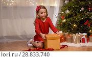 Купить «happy girl opening christmas gift at home», видеоролик № 28833740, снято 26 июля 2018 г. (c) Syda Productions / Фотобанк Лори