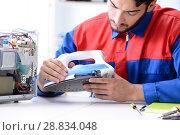 Купить «Man repairman repairing iron at service center», фото № 28834048, снято 11 июля 2017 г. (c) Elnur / Фотобанк Лори