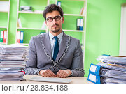 Купить «Employee chained to his desk due to workload», фото № 28834188, снято 11 мая 2018 г. (c) Elnur / Фотобанк Лори