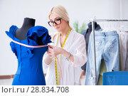 Купить «Woman tailor working on new dress designs», фото № 28834708, снято 13 апреля 2018 г. (c) Elnur / Фотобанк Лори