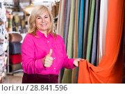 Купить «Female seller demonstrating curtain and showing thumb up», фото № 28841596, снято 17 января 2018 г. (c) Яков Филимонов / Фотобанк Лори