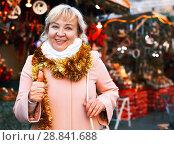 Купить «Positive female in tinsel on Christmas fair», фото № 28841688, снято 27 ноября 2017 г. (c) Яков Филимонов / Фотобанк Лори