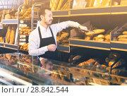 Купить «Baker puts baguettes and bread on the counter», фото № 28842544, снято 26 января 2017 г. (c) Яков Филимонов / Фотобанк Лори