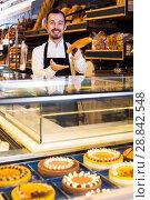 Купить «Seller offering fresh loaf of bread», фото № 28842548, снято 26 января 2017 г. (c) Яков Филимонов / Фотобанк Лори