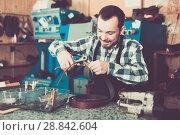 Купить «Man worker working at forming hole in belt», фото № 28842604, снято 2 февраля 2017 г. (c) Яков Филимонов / Фотобанк Лори