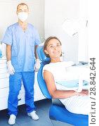 Купить «Girl is sitting satisfied after treatment in dental office», фото № 28842644, снято 10 июля 2017 г. (c) Яков Филимонов / Фотобанк Лори