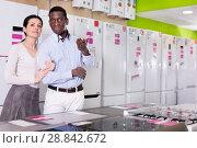 Купить «Couple standing in store of household appliances», фото № 28842672, снято 21 февраля 2018 г. (c) Яков Филимонов / Фотобанк Лори