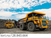 Купить «Large quarry dump truck. Loading the rock in dumper. Loading coal into body truck. Production useful minerals. Mining truck mining machinery, to transport coal from open-pit as the coal production.», фото № 28843664, снято 22 июня 2018 г. (c) Сергей Тимофеев / Фотобанк Лори