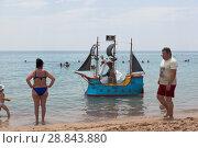 Купить «Мужчина предлагает покатать по воде детей и сфотографироваться на сказочном пиратском корабле на центральном пляже курортного города Евпатории, Крым», фото № 28843880, снято 29 июня 2018 г. (c) Николай Мухорин / Фотобанк Лори