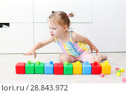 Купить «2 years girl playing with multicolored cubes at home on the floor», фото № 28843972, снято 23 июля 2018 г. (c) ivolodina / Фотобанк Лори
