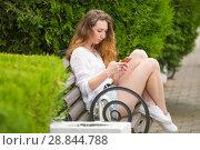 Молодая девушка пишет сообщение в телефоне, на скамейке в парке. Стоковое фото, фотограф Иванов Алексей / Фотобанк Лори