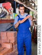 Купить «Seller man is checking quality of tiles», фото № 28860232, снято 26 июля 2017 г. (c) Яков Филимонов / Фотобанк Лори