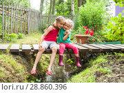 Купить «Счастливые дети на даче сидят обнявшись у ручья», фото № 28860396, снято 21 июля 2018 г. (c) Лариса Капусткина / Фотобанк Лори
