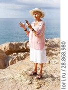 Купить «Elderly woman using phone at seaside», фото № 28868980, снято 6 июля 2018 г. (c) Яков Филимонов / Фотобанк Лори