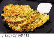Купить «Zucchini pancakes with sour cream on black plate», фото № 28869112, снято 17 августа 2018 г. (c) Яков Филимонов / Фотобанк Лори