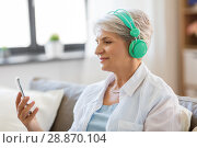 Купить «senior woman in headphones listening to music», фото № 28870104, снято 24 мая 2018 г. (c) Syda Productions / Фотобанк Лори
