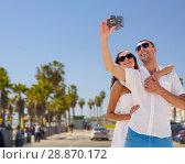 Купить «couple making selfie by camera over venice beach», фото № 28870172, снято 23 июля 2014 г. (c) Syda Productions / Фотобанк Лори