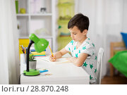 Купить «little boy writing to notebook at home», фото № 28870248, снято 19 апреля 2018 г. (c) Syda Productions / Фотобанк Лори