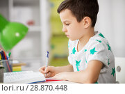 Купить «close up of boy with textbook writing at home», фото № 28870448, снято 19 апреля 2018 г. (c) Syda Productions / Фотобанк Лори