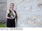Купить «Beautiful girl motorcyclist posing with white helmet leaning stone wall, copyspace», фото № 28870612, снято 16 июня 2018 г. (c) Кекяляйнен Андрей / Фотобанк Лори