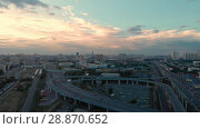 Купить «Flight of the camera over the high-rise buildings, traffic and lights of cars on multi-lane highways. Bright blood red sunset over the city and dramatic clouds and road junction in Moscow», видеоролик № 28870652, снято 29 июля 2018 г. (c) Mikhail Starodubov / Фотобанк Лори