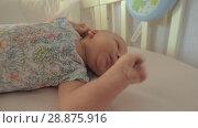 Купить «Newborn girl in crib before daytime sleep», видеоролик № 28875916, снято 21 ноября 2019 г. (c) Данил Руденко / Фотобанк Лори