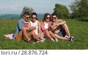 Купить «smiling friends with smartphones sitting on grass», видеоролик № 28876724, снято 19 июля 2018 г. (c) Syda Productions / Фотобанк Лори