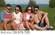 Купить «smiling friends with smartphones sitting on grass», видеоролик № 28876728, снято 19 июля 2018 г. (c) Syda Productions / Фотобанк Лори