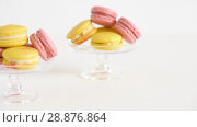 Купить «yellow and pink macarons on glass stands», видеоролик № 28876864, снято 13 июля 2018 г. (c) Syda Productions / Фотобанк Лори